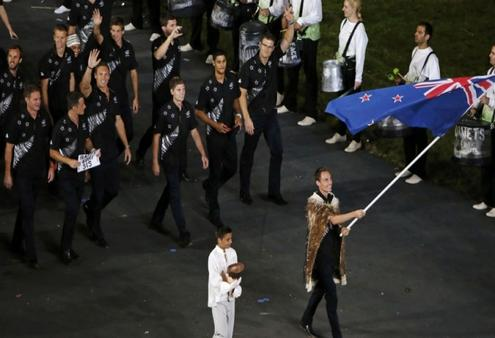 Nick Willis holds the New Zealand flag as he leads the contingent in the Olympic athletes parade. Photo: Reuter