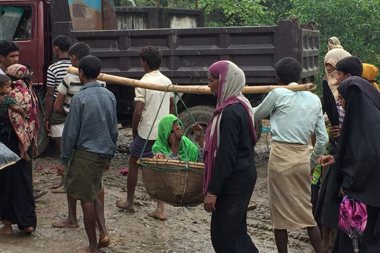 A Rohingya family flees on foot carrying an elderly relative. Photo:Christian Aid.